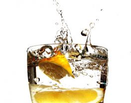 A lemon wedge splashing into a clear glass