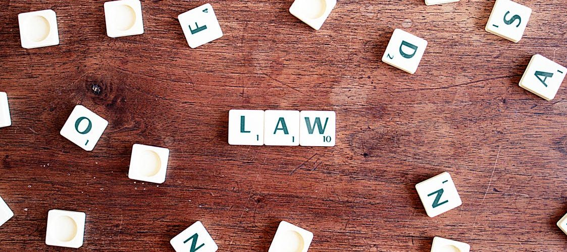 "Scrabble tiles spelling out the word ""LAW"""
