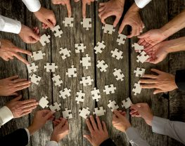 High Angle View of Businessmen Hands Forming Circle and Holding Puzzle Pieces on Top of a Rustic Wooden Table.