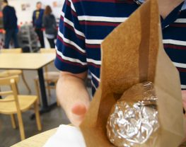 A person in a striped shirt holding a paper bag with an object wrapped in tin foil inside.