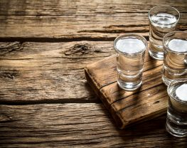 Vodka glasses sitting on an old board on top of a wooden background.