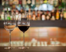 Two tall wine glasses sitting on top of a wooden bar counter in front of a row of alcoholic beverage bottles.