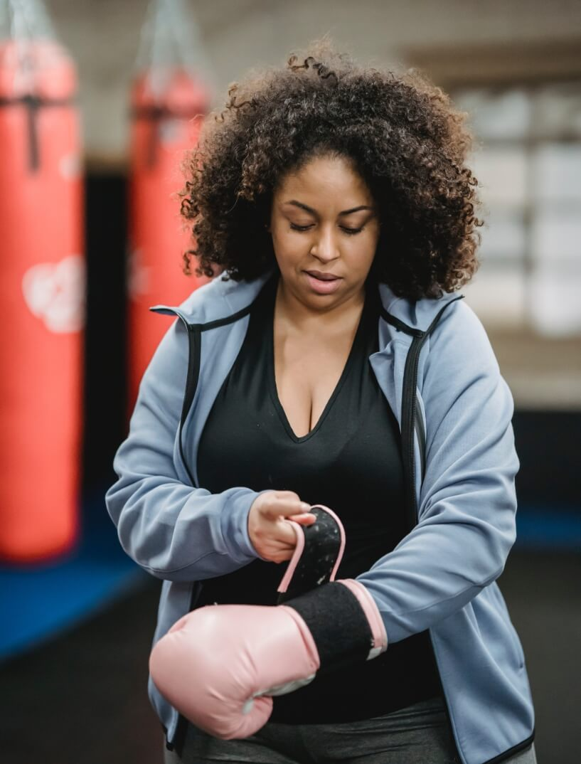 A woman lacing up her boxing gloves