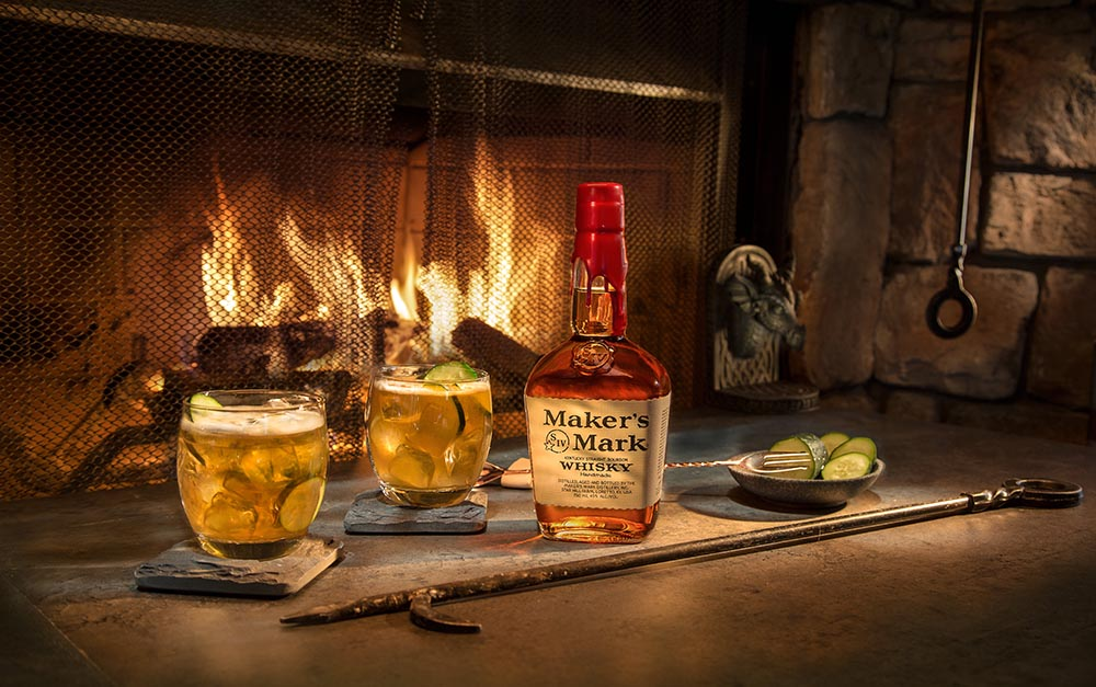 a bottle of makers mark with two glasses next to a fireplace